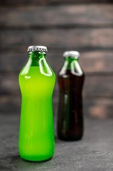 Vorderansicht grüne und schwarze limonade in flaschen