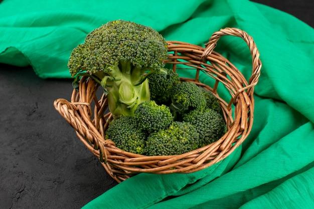 Vorderansicht grüner brokkoli frisch reif im korb auf dem grünen taschentuch und dem grauen boden