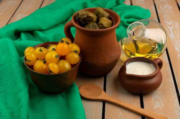 Vorderansicht grünes dolma hackfleischmehl innerhalb des braunen topfes zusammen mit gelbem tomatenjoghurt und olivenöl auf dem braunen rustikalen