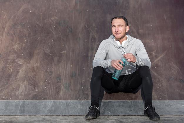 Vorderansicht gutaussehender mann, der eine flasche wasser hält
