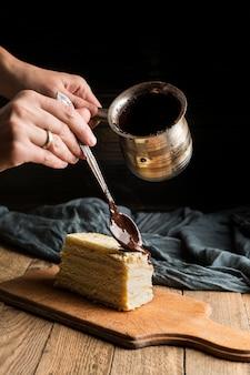 Vorderansicht hand, der kuchen mit geschmolzener schokolade verziert