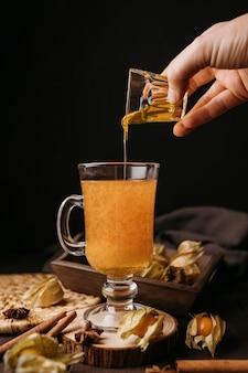 Vorderansicht hand, die honig im heißen wintergetränk gießt