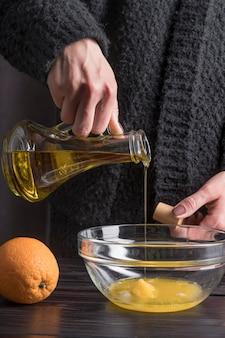Vorderansicht hand, die olivenöl in schüssel gießt