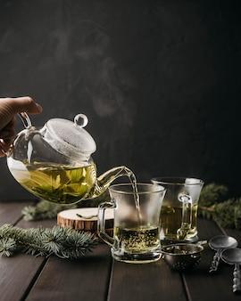 Vorderansicht hand, die tee in glas gießt