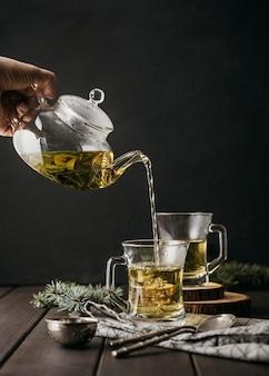 Vorderansicht hand, die tee in glas mit teekanne gießt