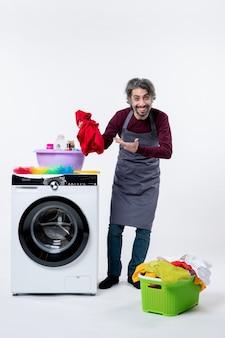 Vorderansicht haushälter mann hält wäsche in der nähe von waschmaschine auf weißem hintergrund isoliert