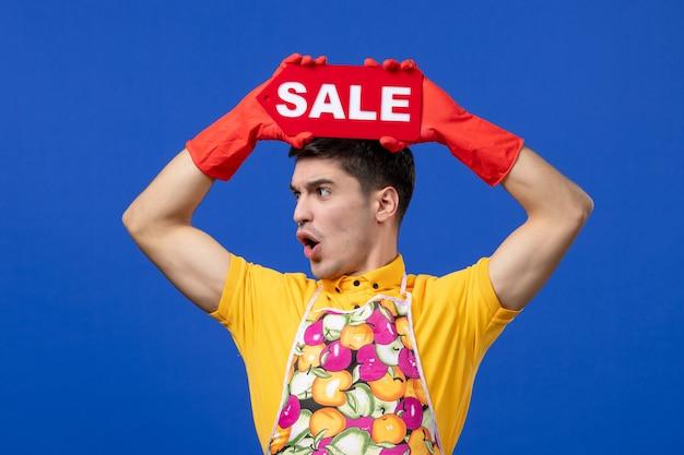 Vorderansicht haushälter mann im gelben t-shirt hebt verkaufsschild über den kopf auf blauem raum