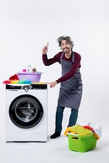 Vorderansicht haushälter mann steht in der nähe von wäschekorb und zeigt auf staubtuch auf weißem hintergrund
