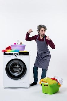Vorderansicht haushälter mann zeigt seine stärke in der nähe von weißer waschmaschine auf weißem hintergrund