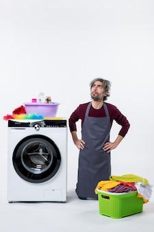 Vorderansicht haushälterin mann kniend neben waschmaschine auf weißem hintergrund nachschlagen