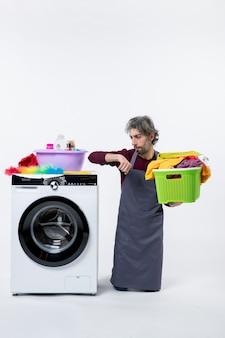 Vorderansicht haushälterin mann überprüfung der zeit mit wäschekorb auf weißem hintergrund