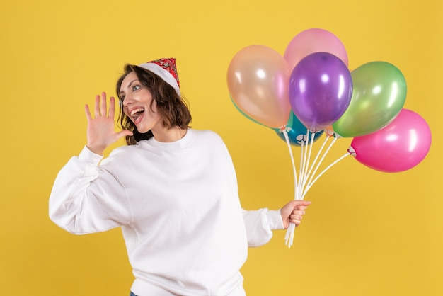 Vorderansicht hübsche frau, die bunte luftballons auf gelb hält
