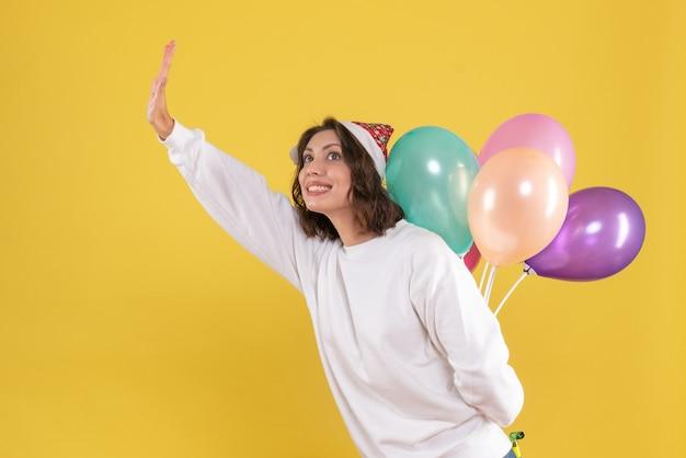 Vorderansicht hübsche frau, die bunte luftballons auf gelb versteckt