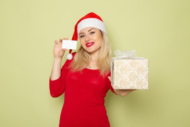 Vorderansicht hübsche frau, die geschenk und bankkarte auf grüner wandfeiertagsweihnachtsschnee-neujahrs-emotionsfarbe hält