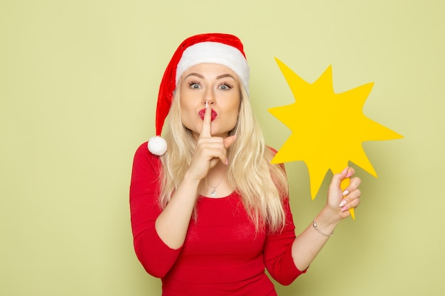 Vorderansicht hübsche frau, die große gelbe figur auf der grünen wand weihnachten emotion schnee neujahr farbfeiertag hält