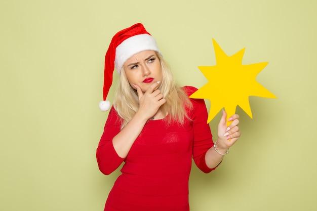 Vorderansicht hübsche frau, die große gelbe figur auf grünem wandweihnachtsgefühl neujahrsfarbfeiertag hält