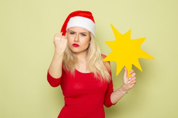 Vorderansicht hübsche frau, die große gelbe figur auf grünen wandweihnachtsgefühlschnee-neujahrsfarbfeiertagen hält