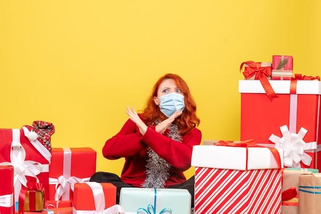 Vorderansicht hübsche frau, die herum sitzt, präsentiert in maske auf gelbem schreibtisch neujahrsfarb-covid-weihnachtsvirus