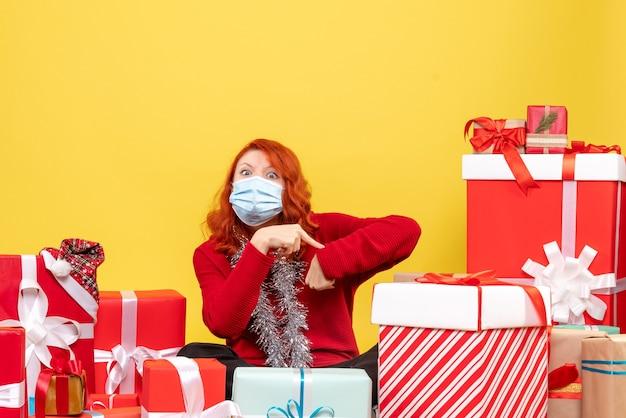 Vorderansicht hübsche frau, die herum sitzt, präsentiert in maske auf gelbem schreibtischvirus weihnachten neujahrs-covid-farbe