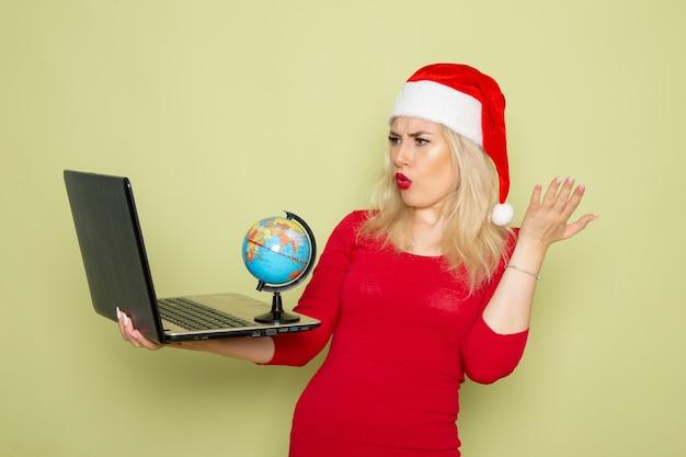 Vorderansicht hübsche frau, die kleine erdkugel hält und laptop auf grünen wandweihnachtsfarbschneefeiertags-neujahrsgefühlen verwendet