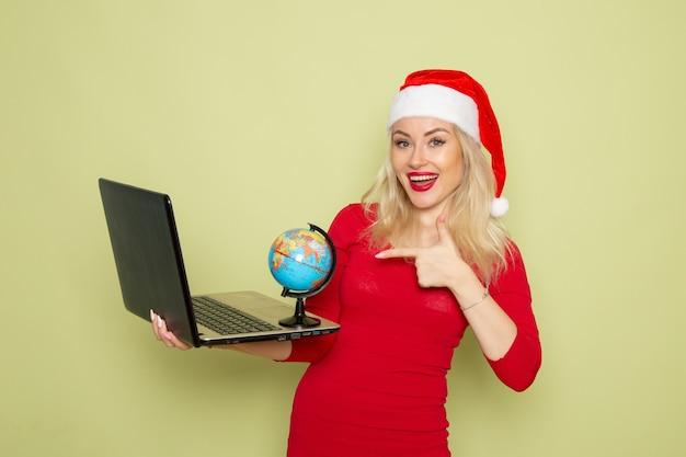 Vorderansicht hübsche frau, die kleine erdkugel hält und laptop auf grüner wandfeiertagsemotion weihnachtsschnee neujahrsfarbe verwendet