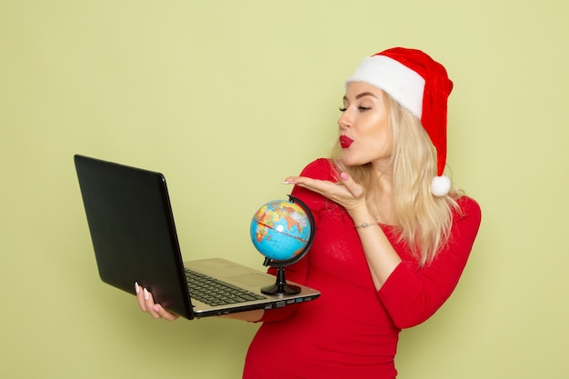 Vorderansicht hübsche frau, die kleine erdkugel hält und laptop auf grüner wandfeiertagsemotionsweihnachtsneujahrsfarbe verwendet