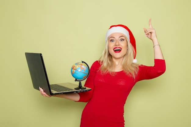 Vorderansicht hübsche frau, die kleine erdkugel hält und laptop auf grüner wandweihnachtsfarbe schnee neujahr emotion verwendet