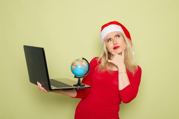 Vorderansicht hübsche frau, die kleine erdkugel hält und laptop auf grüner wandweihnachtsfarbschneeferien-neujahrsemotion verwendet