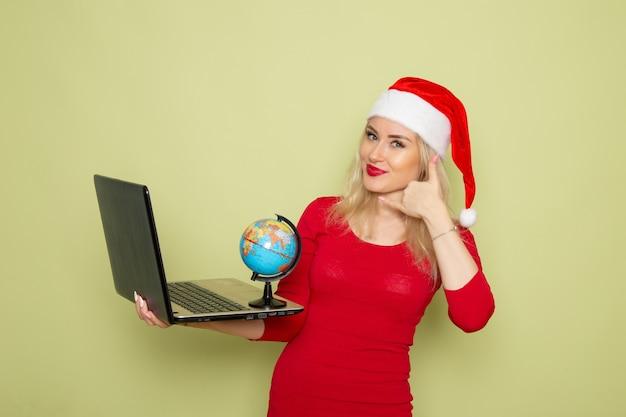 Vorderansicht hübsche frau, die kleine erdkugel hält und laptop auf grüner wandweihnachtsschneefeiertags-neujahrsemotion verwendet