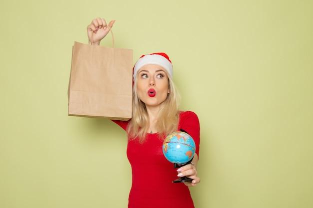 Vorderansicht hübsche frau, die kleine erdkugel und paket auf grünen wandweihnachtsfarbschneefeiertags-neujahrsgefühle hält