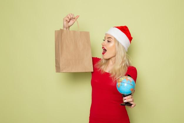 Vorderansicht hübsche frau, die kleine erdkugel und paket auf grüner wandweihnachtsfarbe schneefeiertags-neujahrsemotion hält