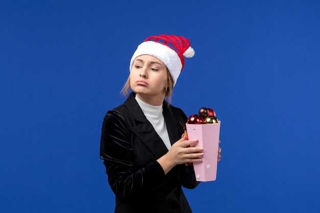 Vorderansicht hübsche frau, die plastikbaumspielzeug auf blauem boden des blauen feiertags-neujahr hält