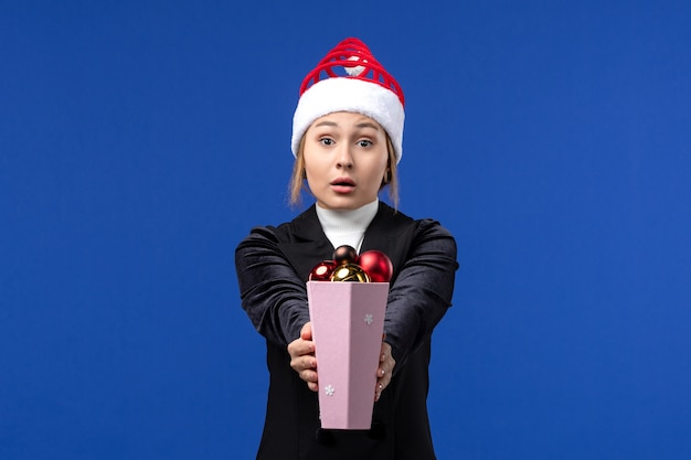 Vorderansicht hübsche frau, die plastikbaumspielzeug auf blauem feiertags-neujahr der blauen wand hält