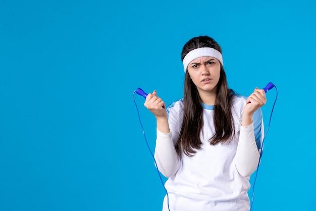 Vorderansicht hübsche frau, die springseil auf blau hält