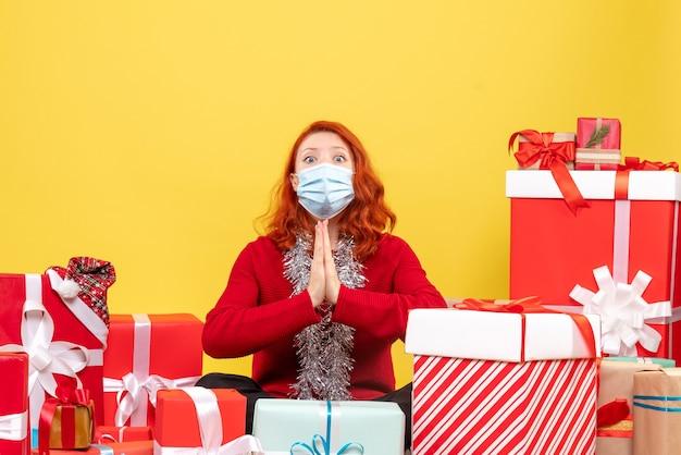 Vorderansicht hübsche frau, die um geschenke in der maske sitzt, die auf gelb betet