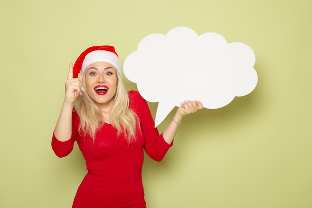 Vorderansicht hübsche frau, die wolkenförmiges weißes zeichen auf grünem wandgefühlschnee-neujahrsfeiertagsweihnachten hält