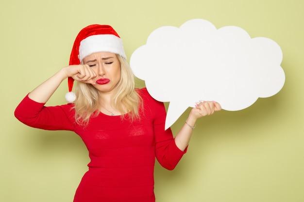 Vorderansicht hübsche frau, die wolkenförmiges weißes zeichen hält, das auf grünem wandweihnachtsschneefoto-feiertagsemotion neues jahr weint