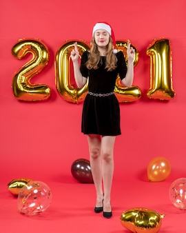 Vorderansicht hübsche frau im schwarzen kleid, die ballons auf rot wünscht on