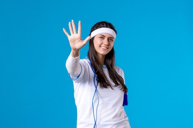 Vorderansicht hübsche frau in der sportkleidung mit springseil auf blau