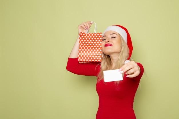 Vorderansicht hübsche weibliche holding vorhanden in kleinem paket und bankkarte auf grüner wandemotion feiertagsweihnachtsfarbe neues jahr