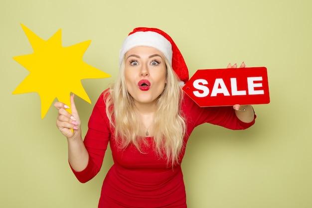 Vorderansicht hübsche weibliche holdingverkaufsschrift und große gelbe figur auf grüner wandschneemotionsfeiertags-weihnachtsneujahrsfarbe