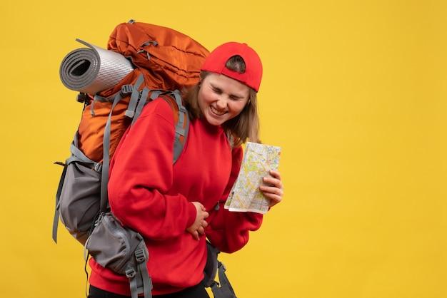 Vorderansicht hübsche weibliche touristin mit rucksack, der hände mit krankem magen hält