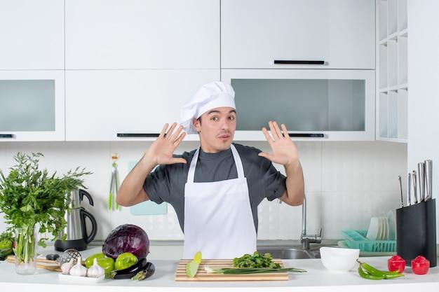 Vorderansicht hübscher männlicher koch in uniformen öffnenden händen