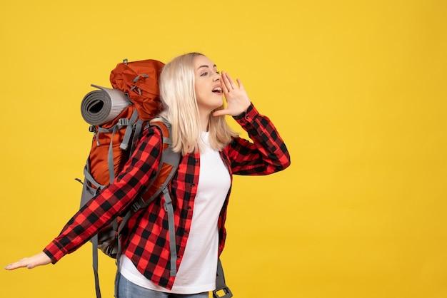 Vorderansicht hübsches blondes mädchen mit ihrem rucksack, der jemanden anruft