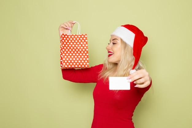 Vorderansicht hübsches weibliches halten, das im kleinen paket und in der bankkarte auf grünem wandgefühlfeiertagsweihnachtsschneefarbe des neuen jahres vorhanden ist