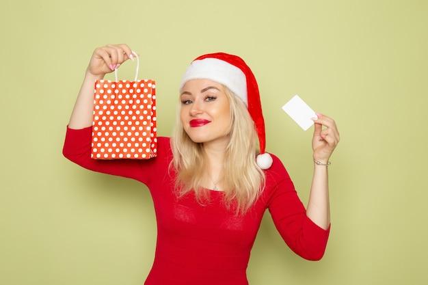 Vorderansicht hübsches weibliches halten vorhandenes in kleinem paket und bankkarte auf grünem wandgefühlfeiertagsweihnachtsschnee färbt neues jahr