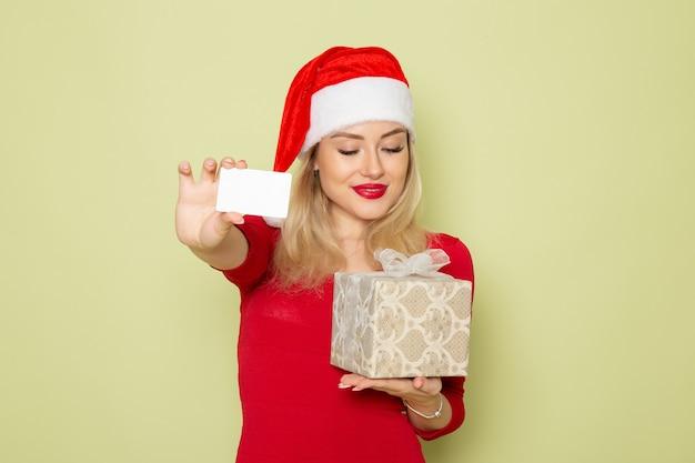 Vorderansicht hübsches weibliches haltengeschenk und bankkarte auf grünem wandfeiertag weihnachten