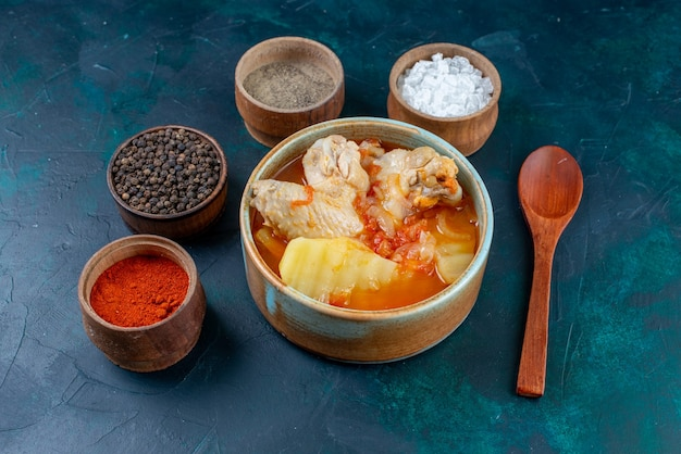 Vorderansicht hühnersuppe mit kartoffeln zusammen mit salzpfeffergewürzen auf der dunkelblauen oberflächensuppe fleischessen abendessen