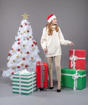 Vorderansicht interessiertes mädchen mit weihnachtsmütze, die rote geschenkbox zeigt