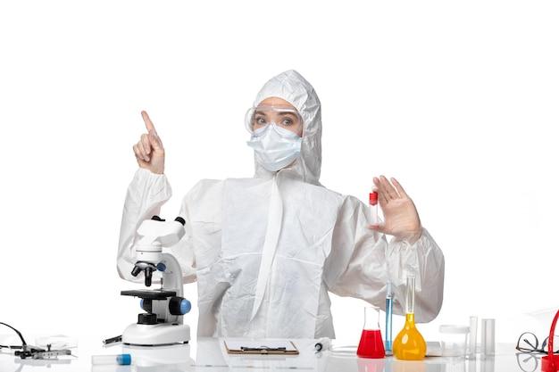 Vorderansicht junge ärztin im weißen schutzanzug mit maske wegen covid halteflasche auf hellweißem hintergrund pandemie splash virus gesundheit covid-
